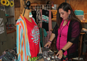 Chrissy Santana arranges merchandise in the Bootique's newly created western wear section. (VBR)