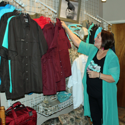 Bootique owner Elma Chavez works on a display of men's hunting apparel, one of the newer lines of merchandise. (VBR)