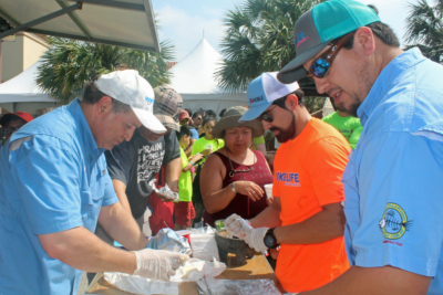 Texas Noble Builders's Rene Capistran and Alfredo Garcia, in light blue shirts, prepare tacos for the participants at a children's fishing tournament in Brownsville. TNB was also a sponsor for the event. (VBR)
