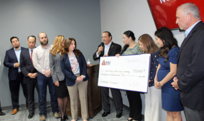 Rene Capistran (with microphone) announces a $25,000 donation to the Our Lady of the Lake University La Feria campus as campus Director Patricia Blanco looks at the check. (VBR)