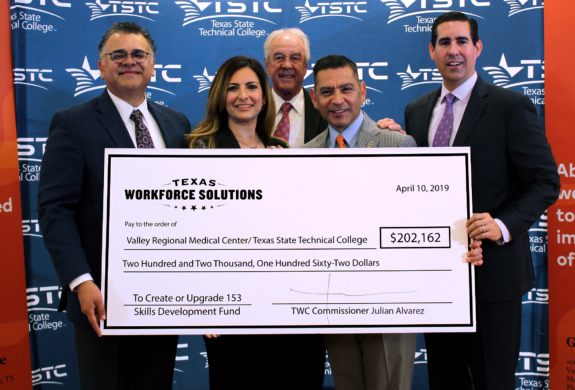 Commissioner Juilan Alvarez presents a Skills development fund check to representatives from Valley Regional Medical Center and Texas State Technical College.