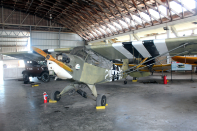 A Piper Cub airplane inside the airport hangar