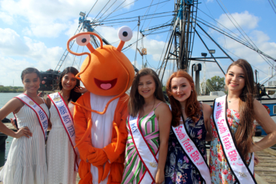 Area queens and a puppet shrimp during the July 9 Blessing of the Fleet ceremony.