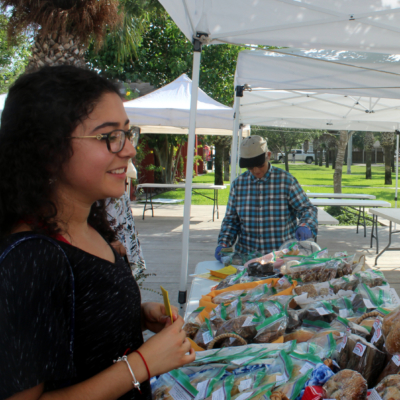 Rebecca de la Garza buys a specialty bread from April Kminiak of Frannys' Garden of Bayview at the Brownsville farmers market.
