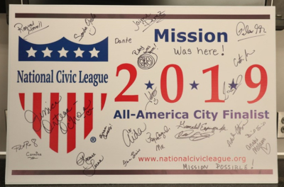 Mission delegation autographs poster board in Denver after learning city had gained the honor.