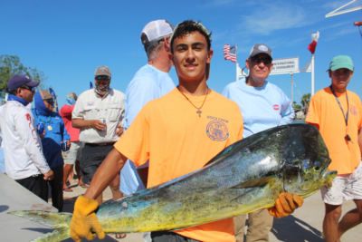 A TIFT deck hand carries a dorado, or dolphinfish, to the weigh-in table.