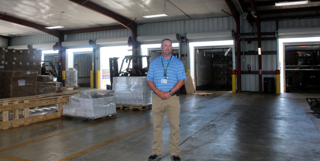 Jason Pettigrew, the company regional sales director, stands by the expanded warehouse at the service center.