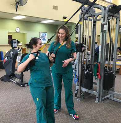 Physical therapy techs Lauren Agado and Michelle Gomez review the correct use of physical therapy equipment at Total Rehabilitation in Harlingen.