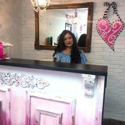 Very Artsy owner, Veronica Cerda-Ayala, stands at her checkout counter, which used to be an old restaurant cashier stand that she transformed by added the molding details on the front and painted in a trendy ombre pattern.