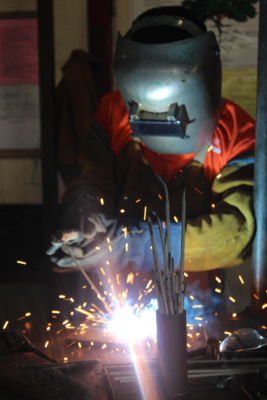 A student welds a pipe as part of a requirements to complete to live at the facility.
