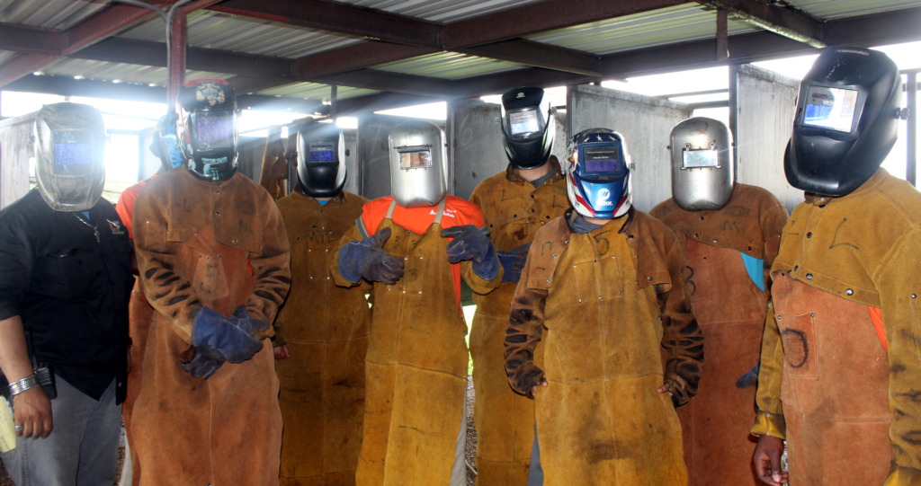 AMIkids Rio Grande Valley students stand by one of their instructors in the welding shop at the Bayview center.