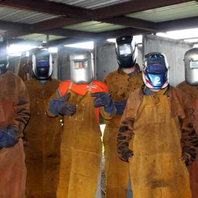 Students stand by one of their instructors in the welding shop at the Bayview center.