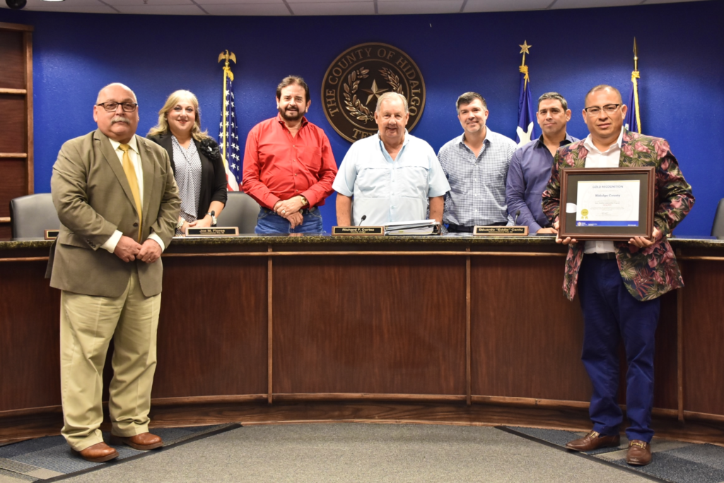 Health Department Public Health Education Coordinator Ricardo Salinas holds the county's Gold recognition. Joining him are department staff and, left, Health and Human Services Chief Administrative Officer Eduardo Olivarez.