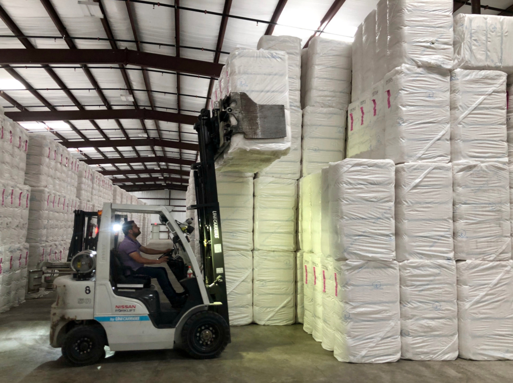Forklift operators work in moving bales to waiting trucks at Commodities Integrated Logistics.