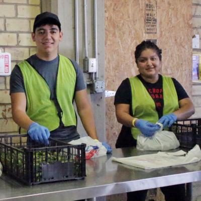 Volunteers Miguel Angel Garza, Leonardo Molina and Maria Garcia sort goods, preparing them to be properly stored and await distribution.