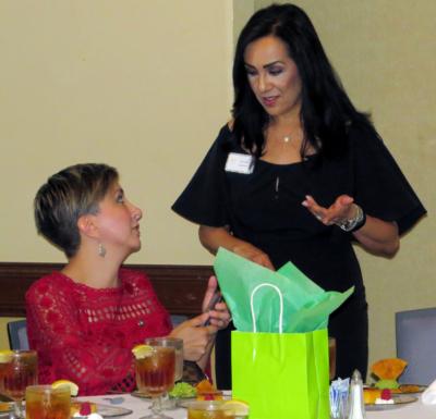 Edna speaks to member Lorraine Frausto during the group's September meeting.