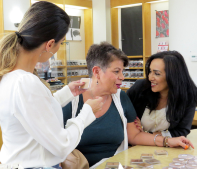 Edna enjoys a quick conversation with customer Irma Burr as make-up artist Yvette Hinojosa matches the foundation best suited for her at Spa La Posada's Matte About Hue event Oct. 15 in McAllen.