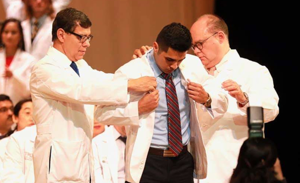 Dr. Leonel Vela, senior associate dean of education and academic affairs, and Dr. John H. Krouse, executive vice president of health affairs and dean of the UTRGV School of Medicine, help Class of 2023 student Roman Silva into his white coat at the White Coat Ceremony July 27. (Courtesy Diane Nixon)