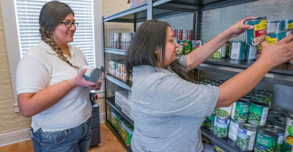Social work major Jacquelyn Herrera, manager for the Student Food Pantry on the UTRGV Brownsville Campus, and Cristina Vega, program coordinator of the UTRGV Student Food Pantry, restock shelves. At UTRGV, student food pantries on both the Edinburg and Brownsville campuses work year-round to help ease food insecurity for university students. (UTRGV Photo by David Pike)