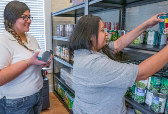 Social work major Jacquelyn Herrera, manager for the Student Food Pantry on the UTRGV Brownsville Campus, and Cristina Vega, program coordinator of the UTRGV Student Food Pantry, restock shelves in the pantry. At UTRGV, student food pantries on both the Edinburg and Brownsville campuses work year-round to help ease food insecurity for university students. (UTRGV Photo by David Pike)