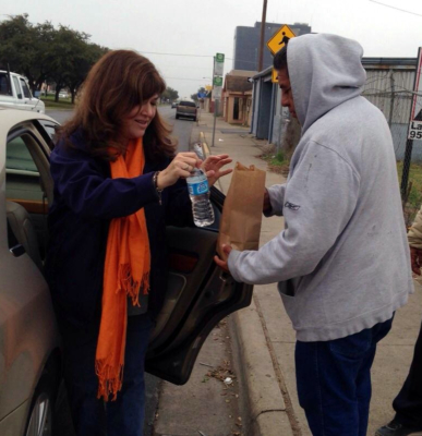 A local volunteer delivers a sack lunch to a person in need. (Courtesy)