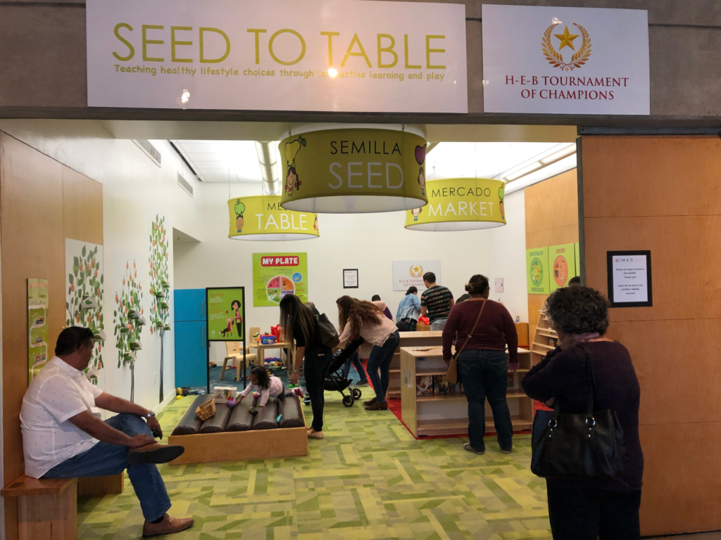 "Families play in the new ""Seed to Table"" hands on exhibit at IMAS."
