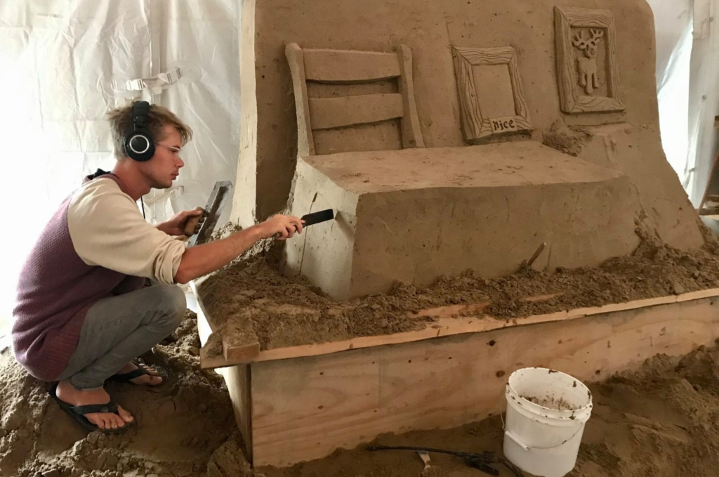 Artist Emerson Wierenga Schreiner creates Santa's workshop from a large block of sand. (Courtesy)