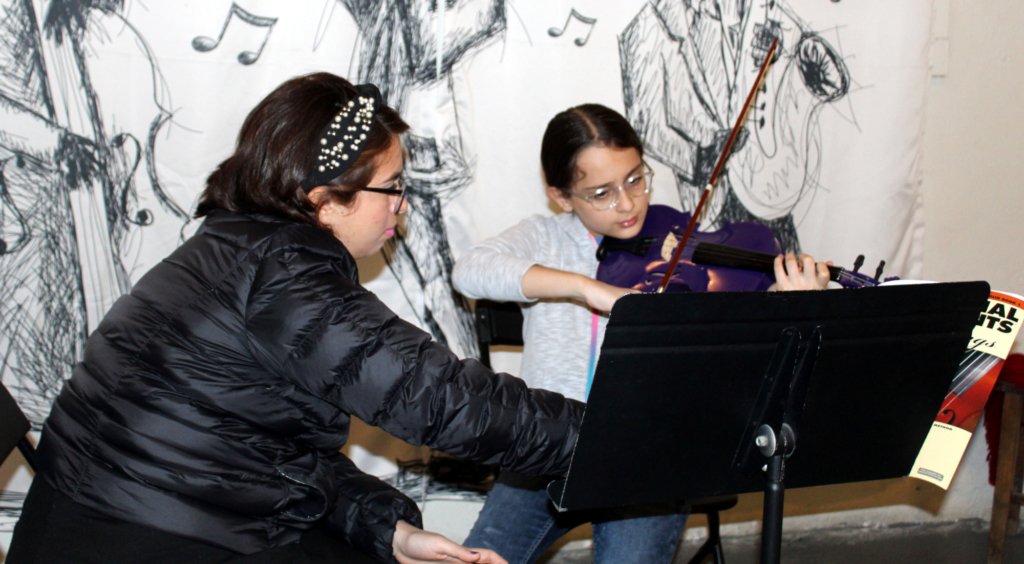 A young student takes a violin lesson from Georgette Garcia at the Carlotta K. Petrina Cultural Center.