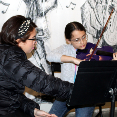 A young student takes a violin lesson from Georgette Garcia.