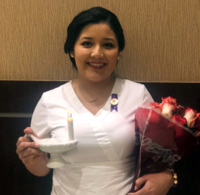 Aime Bautista, who graduated from South Texas College in Dec. 2019 with an associate's degree in nursing, holds a candle at STC's ceremony recognizing new nurses. The candle, when lit, is symbolic of a nurse passing on the flame of hope, service, compassion and peace.