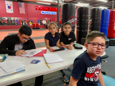 Students complete homework during the after-school program at Team Tiger Martial Arts.