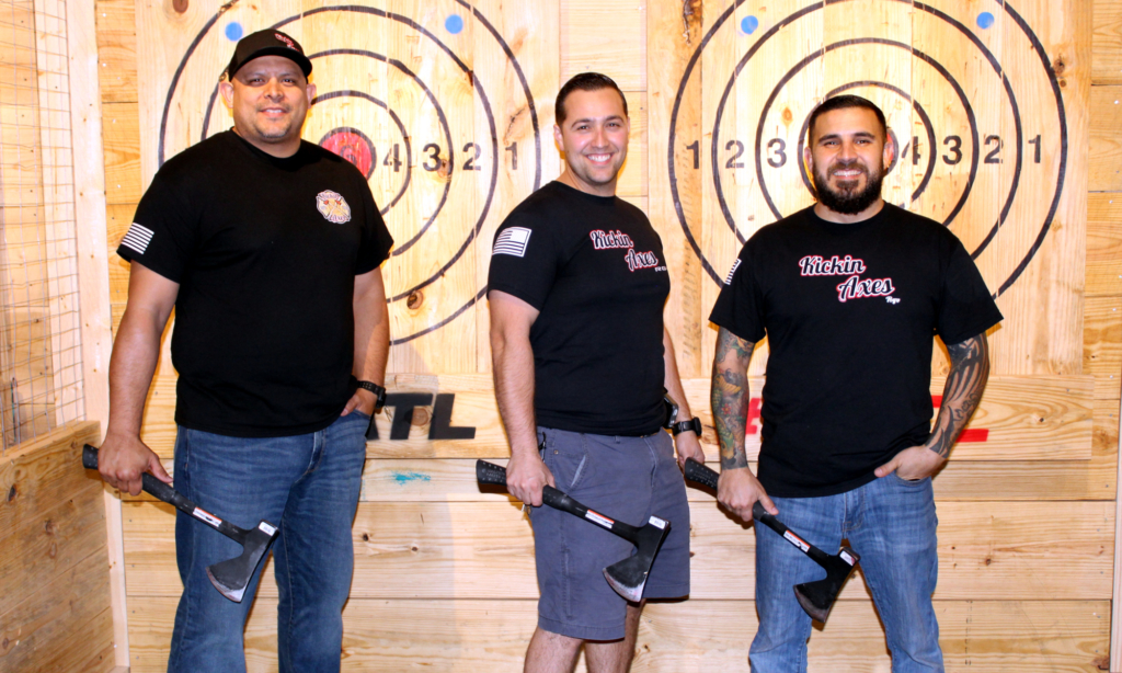 Owners Mark Koite, Jeremy Jensen and Aaron Vera bear their axes while standing in one of the double-target stations at Kickin Axes RGV in McAllen.