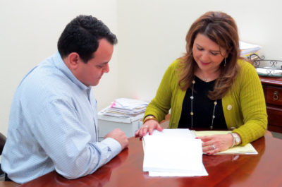 Lorena Castillo-Saldaña goes over a client's file with one of her associates, Nathan Negrete, at Negrete & Castillo LLP.
