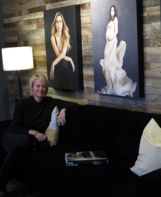 Nicole Gates sits on the black-velvet couch in the lobby area of Nicole Gates Photography, with two of her portraits in the background, her camera in her hands, and a Peter-Lindbergh book beside her.
