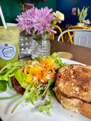 "The ""Love"" sandwich at The Healing Factory is vegan grilled cheese with avocado and hummus and is served with a side salad. A healthy cold-pressed juice always goes well with it."