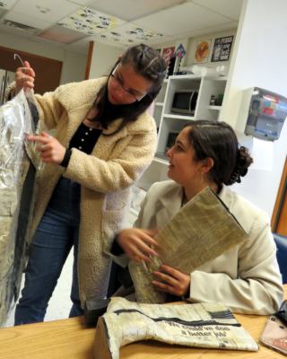 Denisse Damken, left, points out a detail on the Modern Chaos recycled blazer, covered in newspaper, to Gisselle Costa, who is holding a coordinating pair of recycled boots.