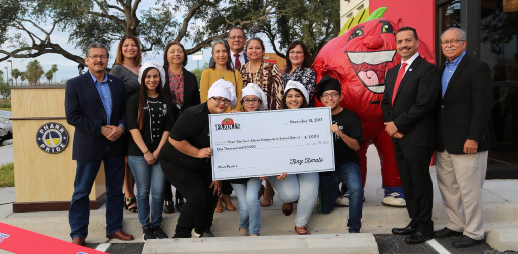 Mayor Ambrosio Hernandez, the Pharr City Commission and PSJA ISD Culinary Arts program students accept a donation from Fazoli's during their Grand Opening celebration in Pharr.