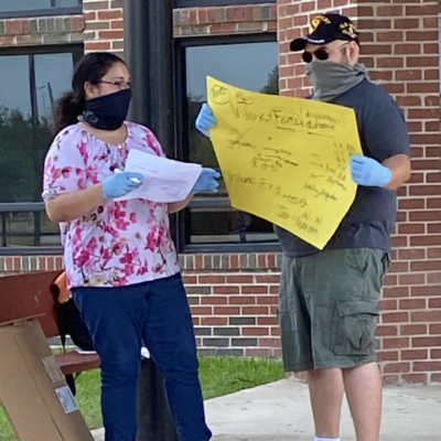 Physics teacher Roxana Merino, with the assistance of her husband, teaches a student outside Mercedes High School on May 8.