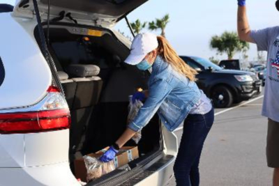 Olivia Lemus places food in the back of an SUV during a pop-up distribution at Bert Ogden Arena. (photo Rosie Martinez, Food Bank of the Rio Grande Valley)