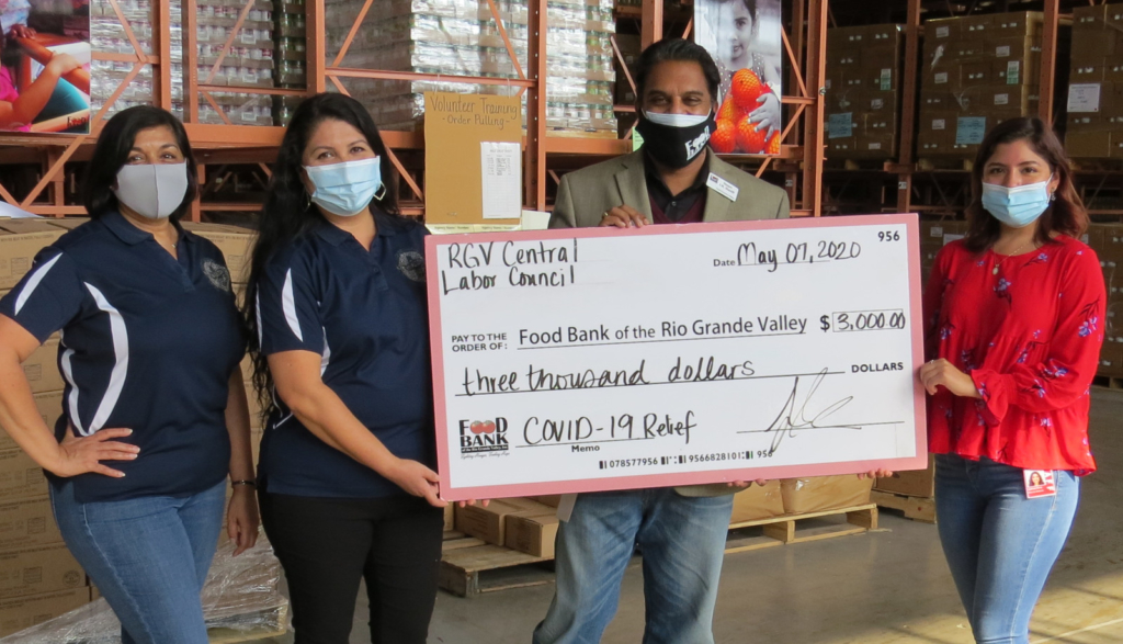 Indeera Mohammed and Sylvia Tanguma present a check for $3,000 to Stuart I. R. Haniff and Gabriela Parra. (VBR)