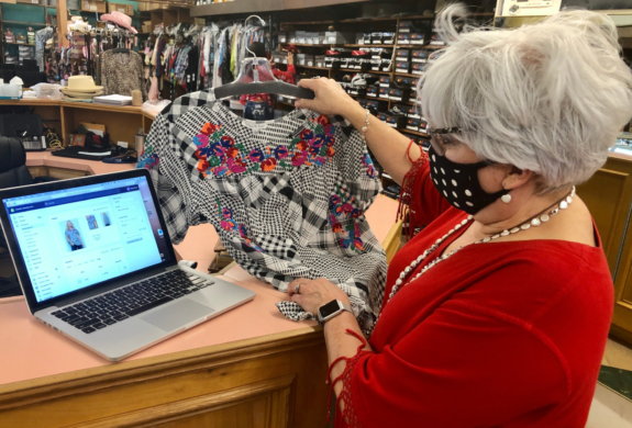 Sandy Pena looks over inventory she wants to feature on her store's website.