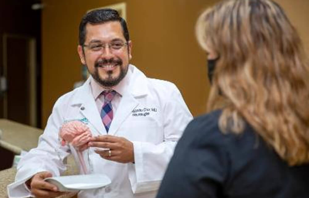 Dr. Alejandro Cruz uses a model of the brain to discuss how lesions form in patients with multiple sclerosis.