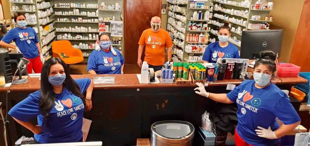 The staff of Coach's Pharmacy in Mercedes, with its owner Gilbert Gomez, center, in his custom orange. (Courtesy)