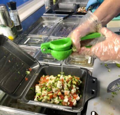 Squeezing finishing touches onto a ceviche plate.