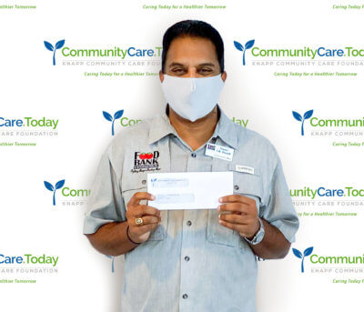 Stuart Haniff, Food Bank RGV CEO, with a $14,952 grant check from the Knapp Community Care Foundation.