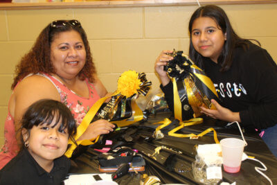 A family learns to make homecoming mums and garters at the Santa Rosa High School ACE center.